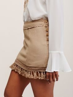 Hot Trot Mini Skirt | Woven cotton mini skirt featuring tassel trim and exposed button closures on the side. Unfinished trim.