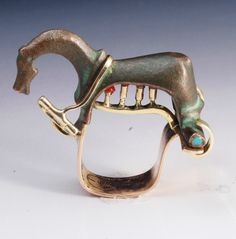 "Ring by Joseph Gatto, who ""recycles"" ancient creations into new pieces. 18kt rose gold, yellow gold, ancient bronze Roman fibula (brooch), turquoise, dyed coral."