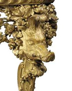 A PAIR OF GEORGE II  ( Detail leg )  GILTWOOD CONSOLE TABLES IN THE MANNER OF THOMAS JOHNSON, CIRCA 1745-55 Each with a later rectangular red and white-bordered marble top above a gadrooned frame and central satyr mask wrapped and surrounded by pierced fruiting vines, with boars' heads to the corners and curving acanthus and vine-wrapped supports terminating in paw feet  Sold 265,875 GBP