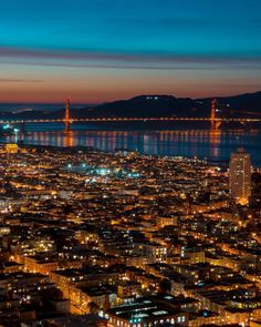 San Francisco at night with the Golden Gate Bridge in the distance.