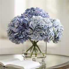 Hydrangea blossoms in mixed shades of soft blue make up this classic elegant bouquet inserted into a glass cylinder vase. Liquid Illusion fake water adds additional realism. Faux floral, no watering ever needed!