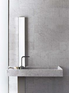 #  I like the vertical lines in these large format tiles.Nice minimal sink too. looks like the pipes are hidden in a support column that follows the line of that narrow mirror.  Alfredo Salvatori / Raw by Piero Lissoni