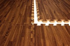 Interlocking Foam Mats that look like wood. Great for a basement. Soft, water resistant, and easy to pop up if it gets damage.