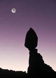 The sun's light reflecting off the earth lights up the shadowed side of a crescent moon under Balanced Rock just before dawn in Arches National Park, near Moab, Utah, USA