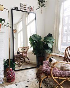 Un grand miroir appuyé contre le mur derrière la chaise à côté de la fenêtre.