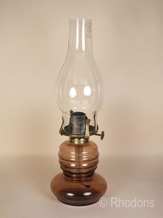 Attractive antique glass oil lamp. Light aubergine coloured glass reservoir with clear glass chimney. British made lamp brass gallery & burner.