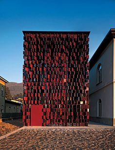Municipal Library in Nembro, Italy by Archea Associati.  A  transparent glass volume is surrounded by a façade of 40×40 cm red  glazed earthenware tiles held in place by a frame of steel  profiles. a construction method that enables the tiles to rotate and so  act as a sunscreen for the glazed inner façades. The result is a  distinctive 'screen' wall in which closed and open planes alternate in  a continuous pattern created by the rotating ceramic elements.