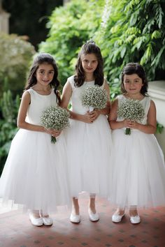 Flower girls in tulle skirted dresses carrying baby's breath posies.