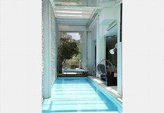 Não há paredes entre a sala e a piscina. A porta de vidro basculante serve para barrar o frio na sala quando a raia não está em uso. A piscina tem revestimento de vidro encapsulado e a parede é de mosaico português irregular
