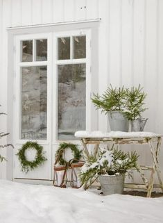 A beautiful snowy white porch!! Evergreens  filled into galvanized buckets finish the Wintery feel!!