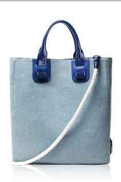 The handbag crafted in denim, featuring tall bucket design with light blue color, twin contrast color grab handles fastening to the top with patch detail, top magnetic snap closure and long detachable shoulder strap.