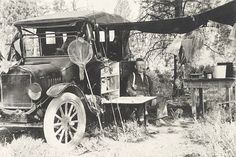 1920s vernacular photo snapshot of no nonsense pipe smoker sitting in Pacific Northwest forest auto campsite alongside Model T Ford touring car 1922 Oregon license plate with fishing rods and reels and long neck net leaning against it, frayed American flag pennants on radiator, running board commissary box with fold-out table erected, canvas tarp tied overhead between car and trees, free standing camp table with enamel bucket, stuff hanging from clothesline.