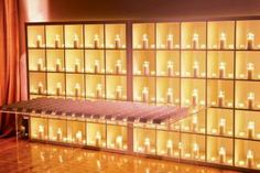 Lindsay Landman Events placed a display of candles in white shelves behind a clear table holding escort cards.