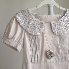 Peter pan collar - check! Scallop shape- check!  Buttons- check Cream color- check!   I love this so much.