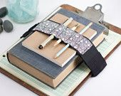 A strap fitted with small loops for carrying pens, pencils, and other handy tools wrapped around a journal, planner, or other book.