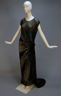 TRAINED BEADED and SEQUINNED GOWN, c. 1930. Black net tabard style with open side to the waist and on left side of skirt, having a sunburst of large and small black sequins and bugle beads radiating from the left hip with a raised center, angled train, floral lace hem band with seed beads.