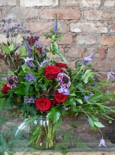 A wild arrangement in a storage jar with red Naomi Roses, accompanied with beautiful seasonal purple and lilac flowers and trailing foliage.