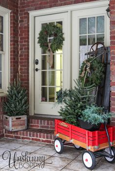 Pretty back porch decorated for Christmas with vintage Radio Flyer wagon and an old sled.