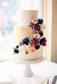 A three-tiered white wedding cake adorned with a flourish of deeply-hued, country-chic blooms by d'Elissious Cake Studio.