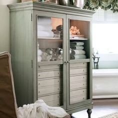 """Showcase family heirlooms and curios in this lovely 2-door display cabinet. 8 interior drawers stow linens, flatware, and more, while 2 lighted shelves highlight decor in country-chic style.  Product: Display cabinet Construction Material: Wood and glass  Color: Spanish moss Features:    Part of the Paula Deen Home Collection Distressed finish Eight drawers  Top drawers include silverware trays Adjustable interior shelving   Accommodates: (2) Canister lights - included    Dimensions: 66"""" H x..."""