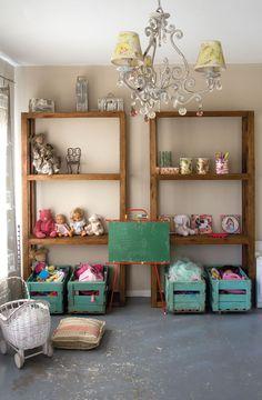 Practicidad y estética van de la mano en el cuarto de juegos. Una cortina de lino con estampa de jaulas y pájaros (Textiles del Sur) tamiza la luz. Al costado, dos bibliotecas diseñadas por Yofre acomodan muñecas y cajones de verdura pintados devenidos en canastos para juguetes. En el piso, un cochecito de mimbre (Puerto de Frutos) y un almohadón a rayas (P. y A. Ricci) suman el toque artesanal, y en el techo, una araña de caireles (Mercado de Pulgas) con pantallas (Lu Madero) aporta glamour…