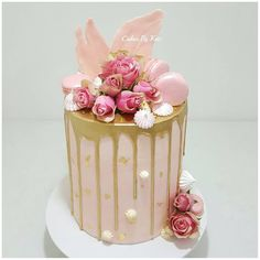 Pink and gold drip cake with gold leaf, macarons , meringues, fresh roses & chocolate shards