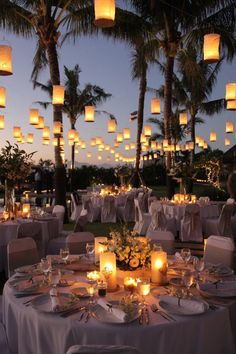 Countless numbers of hanging golden #lanterns light up an outdoor wedding reception