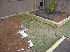 Easily kill grass or weeds by laying down newspaper then mulch.  This was done for our pathways in between the raised garden beds.  It also hides the automatic watering system.