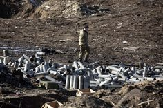 A fighter with the separatist self-proclaimed Donetsk People's Republic army looks for ammunition in a destroyed Ukrainian army compound in the town of Debaltseve, Ukraine February 22, 2015. REUTERS/Baz Ratner