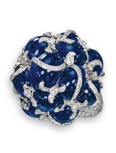SAPPHIRE AND DIAMOND RING, MICHELE DELLA VALLE Stylized floral design, the cabochon sapphire cluster decorated with brilliant-cut diamond scrolls, the mount pavé-set with similar stones, mounted in white gold, signed MdV and numbered.