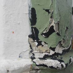 Flaky paint | Worn wall surface | Peeling layers | Green black white | Old