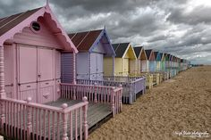 Pastel coloured Beach huts and the dark sky of a gathering storm at West Mersea, Essex, England BY Nigel Blake