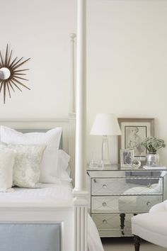 James Michael Howard     Love the white paint wallcolor and chic white poster bed with the starburst sunburst antique bronze mirror above the bed. The sleek mirrored nightstand chest is fabulous! Glass lamp and pretty art finishes the vignette! white bronze silver blue gray bedroom colors.