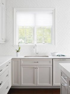 White and gray kitchen features light gray shaker cabinets painted Benjamin moore Smoke Embers paired with white marble countertops and a glossy white herringbone tile backsplash installed sideways.