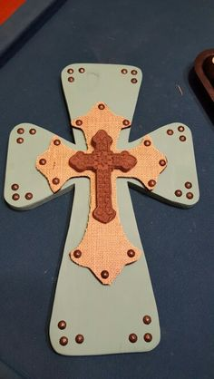 New cross design This cross is 18 inches tall and 11.5 inches wide. The bottom layer is painted in turquoise and with buttons around corners.The top cross is painted black with burlap on top. The third top is a metal cross.These can be painted to your color liking and can be in any color combination. It will have hanger on the back.