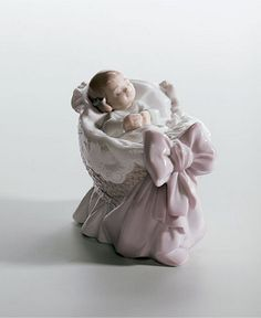 """A sweet baby girl in a basket, just welcomed into the world. Crafted by Lladro, Spain's most esteemed artisans of porcelain figurines.   Porcelain   Hand wash   3 1/2"""" x 2 3/4""""   Gloss finish   Perfec"""