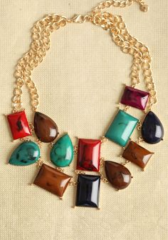 Elegant, marbleized stones in shades of emerald, cognac, crimson, midnight blue, and aubergine are linked together on this gold-toned necklace for a dramatic statement.