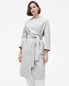 Collarless and elegantly tailored coat with a slightly oversized fit reaching just below the knee. An ideal transitional piece, featuring a cropped sleeve and concealed front button closure. Wear it with the matching tie-belt to accentuate the waist or op