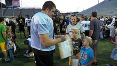 Western Michigan's #67 offensive Lineman, Terry Davisson, signs autographs on Fan's Appreciation Day.
