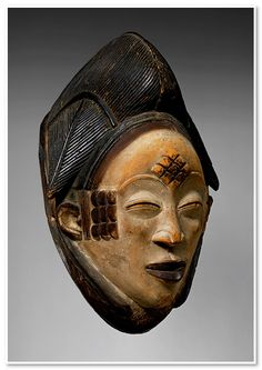 In the Punu communities of southern Gabon, mukudj masks are considered portraits of an exceptionally beautiful female member. The coiffure, featuring a prominent sagittal lobe flanked by two lateral tresses, is a classic style of dressing women's hair practiced throughout the region during the nineteenth century. Lozenge cicatrization markings were incised on the forehead and temples of Punu women as a form of aesthetic embellishment and a sign of sensuality.