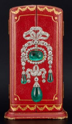 Cartier - A Belle Epoque diamond and emerald brooch. Centring a cabochon emerald, the bows and garlands set with old-cut diamonds, suspending three emerald drops.