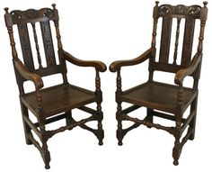 Pair of Edwardian carved oak elbow chairs with pierced cresting at Hunwick Interiors antique furniture showroom, Colchester.