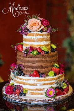 Vanilla and chocolate naked cake with fresh flowers and fresh fruit.