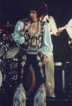 "TENOCHITITLAN OUTFIT! THE KING wearing his spectacular BLACK AZTEC (aka BEAR CLAW, aka CHICKEN BONE) jumpsuit. It's a black suit with light blue puffy sleeves. Also a ""chocker"" is part of the suit. ELVIS first wore it several times during his 1975 July tour and at least once during his following Vegas engagement.  Although an original belt was made for this suit, Elvis didn't wear it when he started using the suit. Instead, he wore the suit with the Blue Armadillo belt."