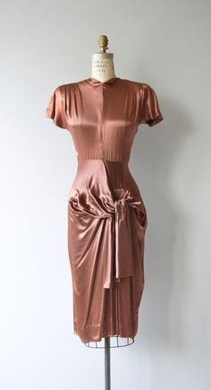 Starlet-worthy vintage 1940s bronze silk dress with high neck, dramatic silhouette with small shoulder pads, fitted waist and hip swag. Metal back zipper. --- M E A S U R E M E N T S ---  fits like: xs/small bust: 35 waist: 25 hip: 38 length: 46 brand/maker: Young Hollywood condition: very good, one small mark on the back of the skirt (pictured) and a few minor snags.  to ensure a good fit, please read the sizing guide: http://www.etsy.com/shop/DearGolden/po...