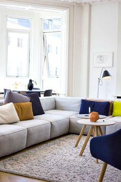 Ambiance décontractée et dans l'air du temps - un canapé et un tapis moelleux, des coussins colorés...: