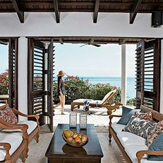 The red and blue color palette in this outdoor living room echo the hues of sea and blooming flowers. Coastalliving.com