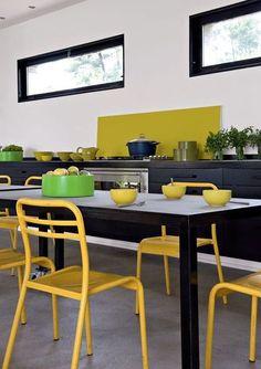 La cuisine noire est réveillée par des touches de jaune.