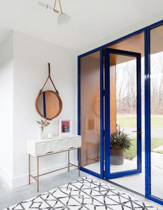white modern home entry with bright blue doorway, white and black tribal rug, gray concrete floor, pantone lapis blue, bright blue, royal blue, sapphire blue