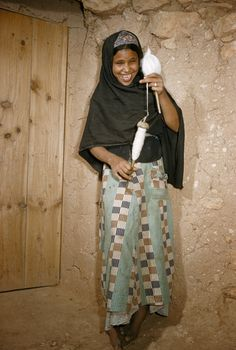 Young girl smiles while showing off her hand bobbin for spinning wool in Goulimine, French Morocco.